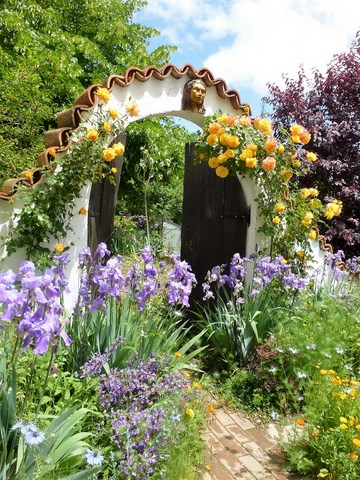 Arched entrance to garden with roses and iris'